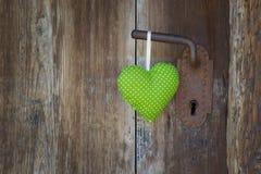 绿色心脏形状垂悬在门把手的-木背景机智 图库摄影