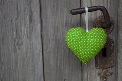 绿色心脏形状垂悬在门把手的-木背景机智 免版税图库摄影