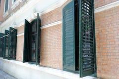 绿色快门和红砖墙壁 免版税库存图片