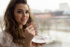 色情透明内衣的性感的少妇喝在窗口基石的茶 在背景的都市风景 免版税库存图片