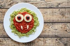 绿色意粉面团创造性的万圣夜食物吸血鬼妖怪用假血液西红柿酱和大无盐干酪眼珠 免版税库存照片