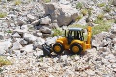 黄色挖掘机儿童的玩具 免版税库存图片