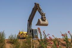 黄色挖掘机在小山站立 库存照片