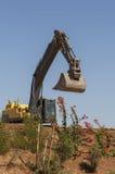 黄色挖掘机在小山站立 免版税库存图片