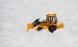 黄色推土机,挖掘机在雪原安置的玩具除雪机, a 免版税库存照片