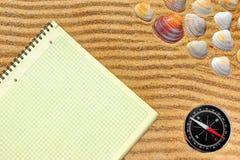 黄色方格的笔记薄和指南针在沙子 库存照片