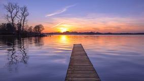 紫色日落全景在平静的湖的 库存照片