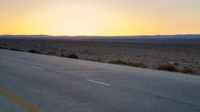 黄色日落和沙漠高速公路在约旦 免版税库存图片