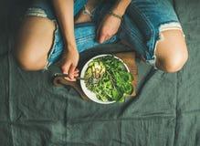 绿色早餐膳食用菠菜、芝麻菜、鲕梨、种子和新芽 免版税库存图片