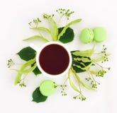 绿色明亮的用在白色背景的花装饰的macarons和茶 平的位置 库存照片