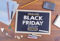 黑色星期五销售额 在木办公桌上的黑板 免版税库存照片