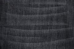 黑色有折叠的使用的牛仔裤在白色 免版税库存图片