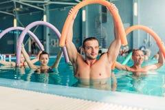 水色有氧运动行使,有男性教练员的妇女 库存图片