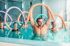 水色有氧运动行使,有男性教练员的妇女 免版税库存图片