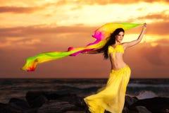 黄色服装的肚皮舞表演者在日出的海滩 免版税库存照片