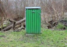 绿色木垃圾桶在有草的森林里 免版税库存照片