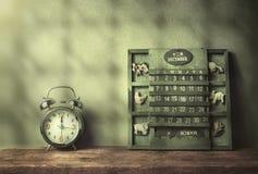绿色木日历葡萄酒和闹钟在木桌结尾  免版税库存照片