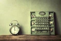 绿色木日历葡萄酒和闹钟在木桌结尾  库存照片