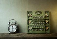 绿色木日历葡萄酒和闹钟在木桌结尾  免版税库存图片