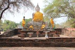 黄色材料在菩萨附近石雕象被装饰了在阿尤特拉利夫雷斯(泰国) 免版税图库摄影