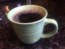 绿色杯子在花岗岩工作台面的咖啡 库存照片