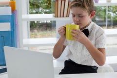 从黄色杯子的商人饮用的咖啡由膝上型计算机 库存照片