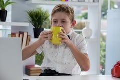 从黄色杯子的商人饮用的咖啡 库存照片