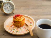 黄色杯形蛋糕投入了一块球状木板材 在杯形蛋糕旁边有葡萄酒闹钟和加奶咖啡杯子 免版税库存照片