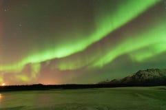 在山和一个冻湖的绿色极光 库存图片