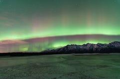 在山和一个冻湖的绿色极光 免版税图库摄影