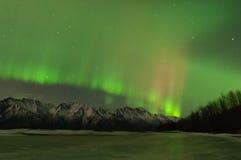 在山和一个冻湖的绿色和桃红色极光 库存照片