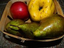 黄色柑橘,红色苹果,在一个木篮子的绿色梨 免版税库存照片