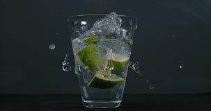 绿色柑橘, aurantifolia的柑橘,落入一杯水, 股票视频