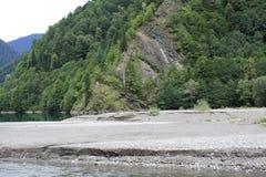 绿色树包围的Mountain湖 库存图片