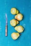 黄色梨和刀子在绿松石木背景 免版税库存照片