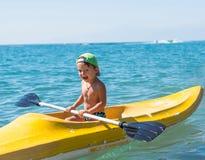 绿色棒球帽的微笑的小男婴划皮船在天时间的热带海洋海的 正面人的情感,感觉, j 免版税图库摄影