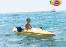 绿色棒球帽的微笑的小男婴划皮船在天时间的热带海洋海的 正面人的情感,感觉, j 免版税库存图片