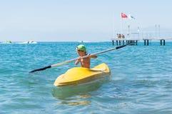 绿色棒球帽的微笑的小男婴划皮船在天时间的热带海洋海的 免版税图库摄影