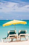 绿色椅子在黄色伞下在天堂 免版税库存照片