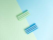 绿色橡皮擦和蓝色橡皮擦在半蓝色和绿色背景 免版税库存图片
