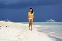 黄色比基尼泳装的女孩走在白色海滩的在风暴天空下 图库摄影