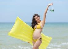 黄色比基尼泳装的孕妇在海滩 库存图片