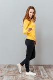 黄色毛线衣的愉快的微笑的妇女有手机的 免版税图库摄影