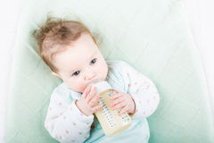 绿色毛线衣饮用奶的逗人喜爱的婴孩从瓶 免版税库存图片