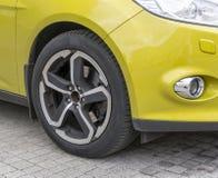 黄色汽车特写镜头-有轻合金外缘的前轮 免版税库存照片