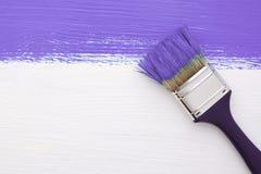 紫色油漆条纹与一把油漆刷的在白色 免版税库存图片