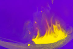黄色油漆的抽象在紫罗兰色背景的以有火的一把匙子的形式 免版税图库摄影