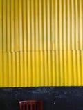 黄色波纹状的金属墙壁 库存图片