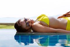 黄色泳装的少妇放下在游泳池旁边的 图库摄影