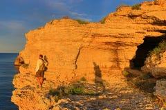 黄色海边峭壁探索人 库存照片